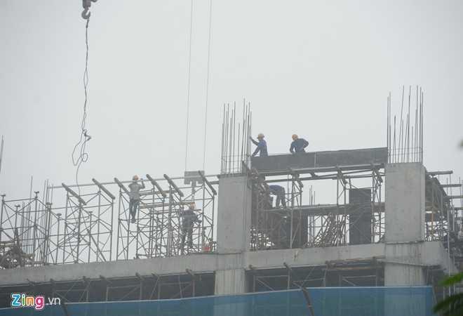 Công nhân công trường xây dựng làm việc trong điều kiện thời tiết không thuận lợi.