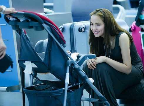 Diễm Hương trông bé Noah trong lúc chồng làm thủ tục tại sân bay.