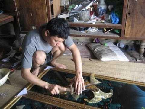 Người thợ đang chế tác bức tranh từ chất liệu sừng trâu