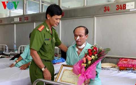 Đại tá Võ Văn Phúc, Phó Giám đốc Công an tỉnh trao giấy khen và thưởng nóng cho ông Hải đang điều trị tại Bệnh viện Chợ Rẫy. Ảnh: Lê Ánh