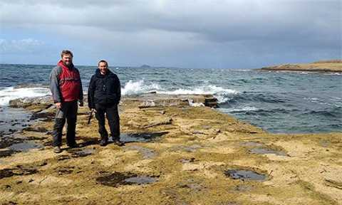 Steve Brusatte (phải) và Tom Challands (trái) tại di tích dấu chân khủng long trên đảo Skye. Ảnh: Mark Wilkinson.