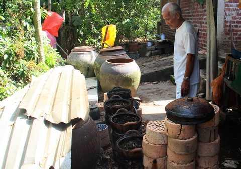 Ông Chín Chạy bùi              ngùi nhìn dãy ông táo nơi vợ ông đã từng chế biến cóc và nấu nước lá cho              ông chữa ung thư