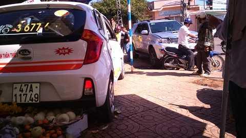 Đuôi chiếc taxi lọt thỏm vào sạp hoa quả (Ảnh: Tây Sơn)