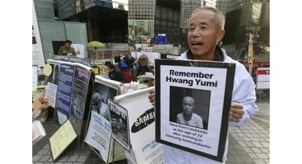 Ông Hwang Sang-gi cầm ảnh con gái qua đời vì nhiễm bệnh sau khi làm việc ở Samsung để phản đối tập đoàn ngày 23/10. Ảnh: AP