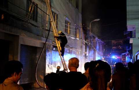 Lực lượng chức năng leo mái nhà khống chế đám cháy.