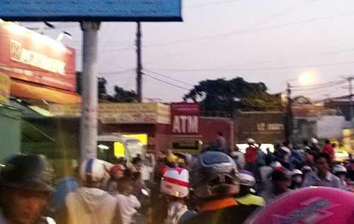 Hàng trăm người đang tập trung trước ngân hàng có tên cướp cố thủ. Ảnh: Thái Hà
