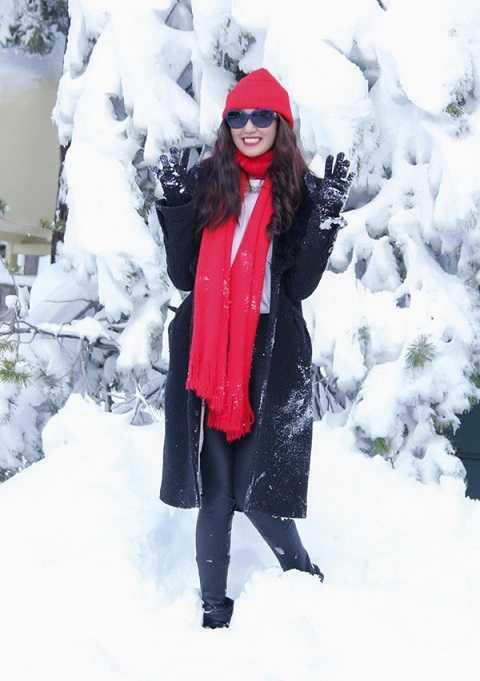 Chỉ cần mũ đỏ, khăn đỏlà đủ tạo nên không khí Giáng Sinh rồi. Phụ kiện giúp Khánh My thêm rạng rỡ và phù hợp với không gian thông xanh, tuyết trắng này.