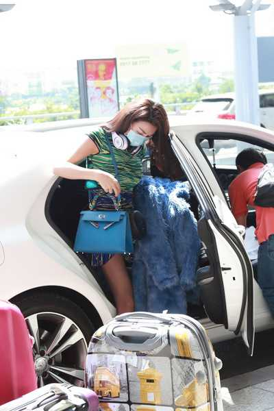 Giữa tiết trời nóng của Thành phố Hồ Chí Minh người đẹp xuất hiện tại sân bay Tân Sơn Nhất trong bộ đầm ngắn trẻ trung xinh đẹp, boot ngắn cổ thời trang, khoác túi Hermes xanh ton sur ton với màu đầm cực kỳ sành điệu và thời trang.