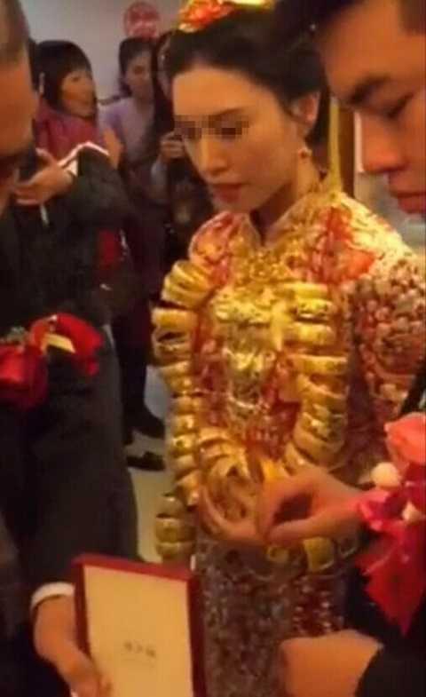 Cô dâu khá vất vả khi đi giữa nhiều vị khách với nhiều trang sức trên người