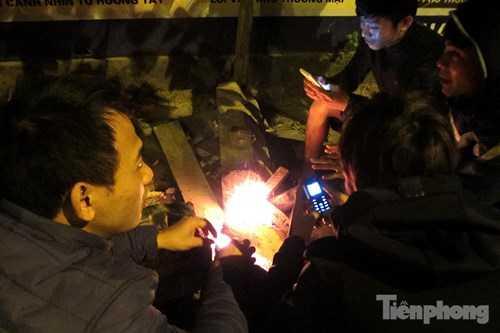 Nhóm bạn trẻ tụ tập bên đống lửa trên đường Nguyễn Xiển (Hà Nội) sưởi ấm.