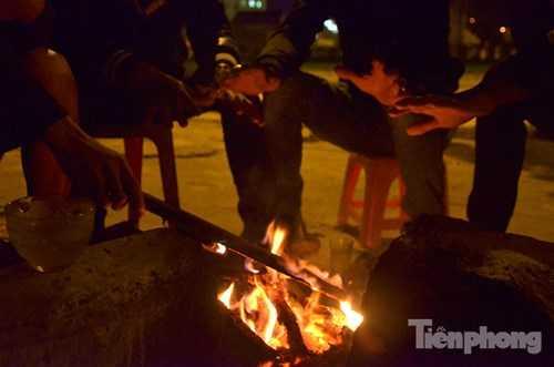 Những bàn tay hơ trên đống lửa để giữ ấm.