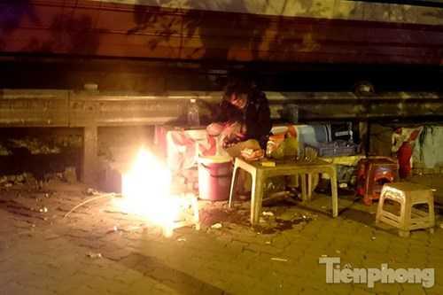 Người bán nước trên đường Giải Phóng đốt lửa sưởi ấm.