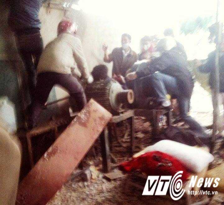 Lực lượng chức năng cùng người dân đưa thi thể nạn nhân khỏi hiện trường.