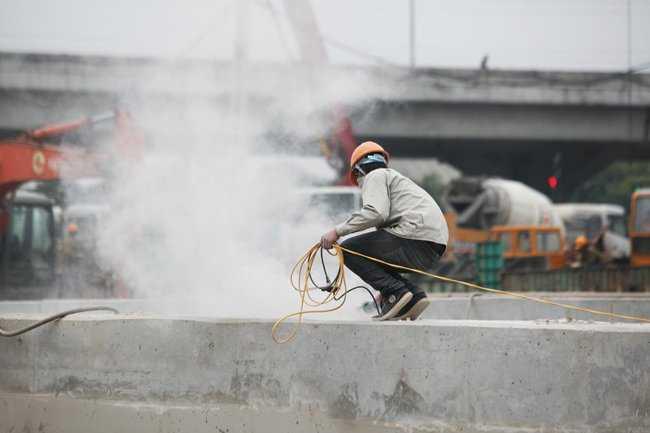 Phía tường bao của hầm chui, một số công nhân đang dùng máy để mài cho bề mặt bê tông bằng phẳng và lắp lan can.