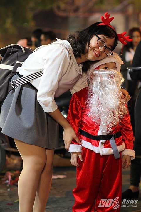 Một ông già Noel nhí tạo dáng cùng du khách trên đường.