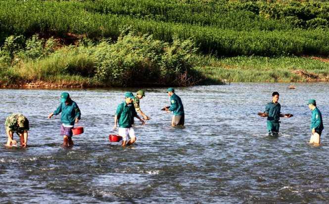 Lực lượng chức năng đang tiến hành trục vớt đầu đạn dưới lòng sông. Ảnh: Lâm Thiên