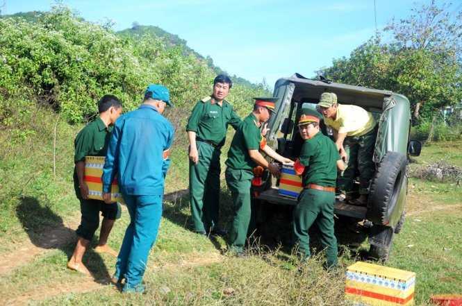 Lực lượng chức năng xếp các thùng chứa đầu đạn lên xe mang đi tiêu hủy. Ảnh: Lâm Thiên