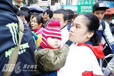 Vẻ căng thẳng và mệt mỏi của hai mẹ con khi phải chen lấn xô đẩy liên tục trong đám đông.