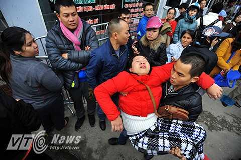 Một người phụ nữ bị ngất do kiệt sức trong đám đông chen lấn xô đẩy. Bà được đưa ngay vào phóng khám để cấp cứu.