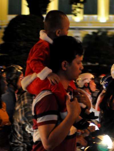 Người bố bồng con trên lưng đi dạo khắp phố phường.