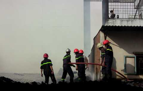 Lực lượng chức năng tiếp cận đám cháy từ mái nhà.