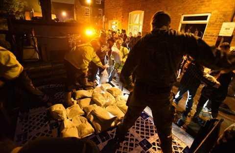 Người dân và binh sĩ Anh đang dùng bao cát chặn nước lũ trên đường Bishopthorp - Ảnh: Asadour Guzelian