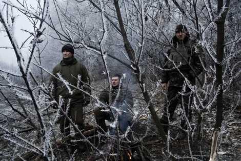 Ba quân nhân Ukraine ngồi bên cạnh những bụi cây bị băng giá bao phủ