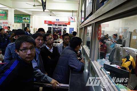 Tại quầy bán vé phía trong sảnh của bến xe, hàng dài người dân xếp hàng chờ mua vé xe về quê.