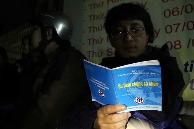 Trong lúc ngồi chờ, anh Trần Xuân Hoàng (quận Thanh Khê) tranh thủ đọc thông tin trong Sổ tiêm chủng cá nhân của con trai 6 tháng.