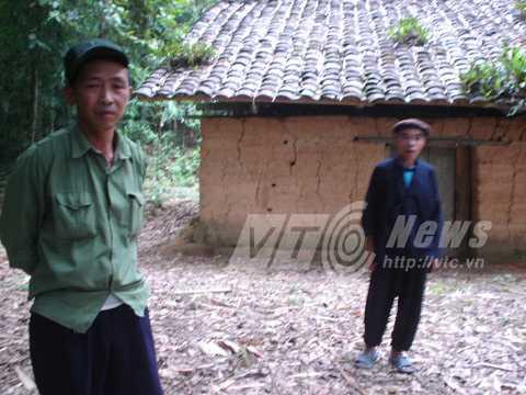 Xã đội trưởng Vàng Sải Phin (phải) và thầy cúng Lù Vần Xẻng trước ngôi đền trong rừng cấm của người Nùng
