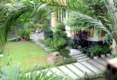 Bên trong căn biệt thự, thiết kế tiểu cảnh tinh tế với khu vườn xanh mát và đường đi lát đá trông rất thanh bình.