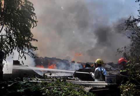 Lực lượng chức năng tiếp cận phun nước vào đám cháy.
