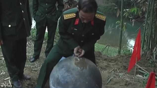 Chuyên gia quân đội Việt Nam bên cạnh quả cầu kim loại từ trên trời rơi xuống