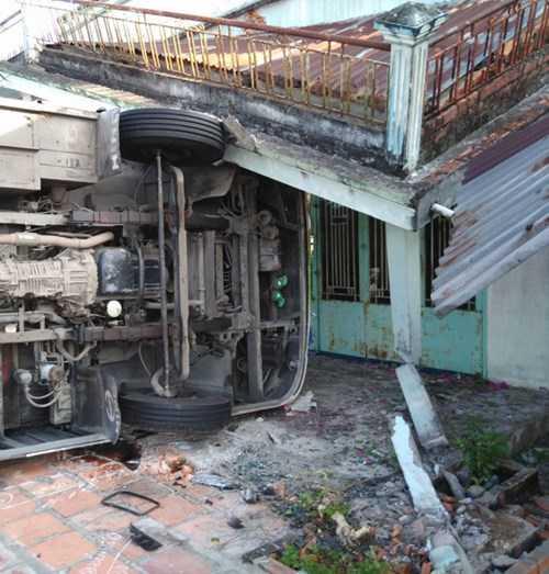 Chiếc xe ô tô khách lật nhào, lao vào nhà dân làm sập mái trước.