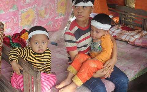 Từ ngày mẹ mất, 2 người con (bên trái và đang được bồng) luôn khóc gọi mẹ
