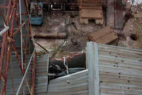 Một mảng tường rộng và mái tôn bị giàn ép đè hư hỏng.