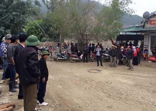 Thân nhân và người dân đứng ngoài phạm vi phong tỏa mỏ đá để ngóng tin. Phía xa xa là mỏ đá, nơi nhóm công nhân gặp nạn. Ảnh: Lê Hoàng.
