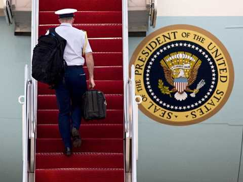Một trợ lý quân sự mang FQuả bóng hạt nhân trên cầu thang chiếc chuyên cơ Air Force One. (Nguồn: businessinsider.com)
