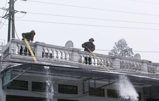 Tuyết rơi dày đặc trên mái nhà khiến người dân phải thường xuyên gạt xuống. Có gia đình còn dùng vòi phun nước nóng lên mái nhà với mục đích làm tuyết nhanh tan.