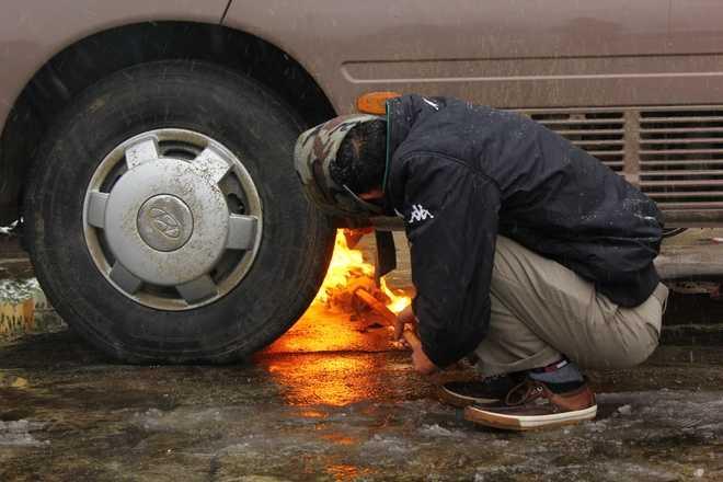 Chiếc xe để ngoài trời vì quá lạnh máy không thể khởi động. Tài xế phải dùng đuốc