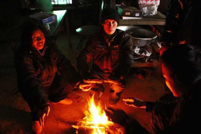Hạn chế ra ngoài, ngồi quây quần bên đống lửa là cách chống rét thông dụng của nhiều người dân Y Tý (huyện Bát Xát).