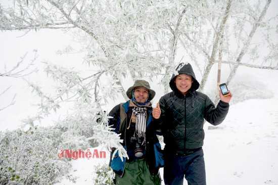 Mọi người thích thú lưu lại những giây phút hiếm hoi trước cảnh băng tuyết ở xã Na Ngoi (Kỳ Sơn). Trong ảnh: anh Hà Văn Khôi (phải) - Ban nông nghiệp xã Na Ngoi cùng dân phượt bên cây đào trước Trạm biên phòng Buộc Mú - đồn Biên Phòng Na Ngoi