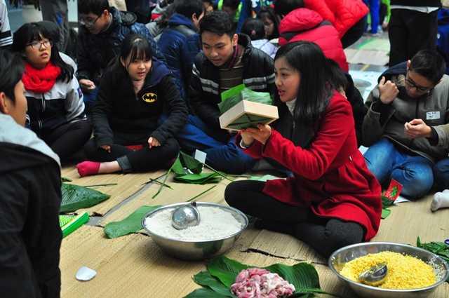 Cô giáo hướng dẫn các bạn học sinh cách gói bánh chưng bằng khuôn.