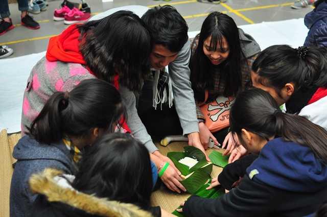 Các nhóm học sinh khéo léo dàn đều lớp gạo, đỗ, thịt vào khuôn lá.