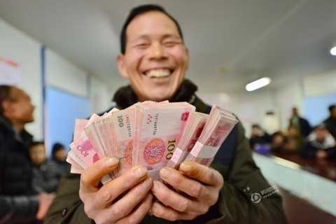 Gương mặt vui vẻ của một nông dân khi cầm 600.000 NDT thưởng Tết trên tay