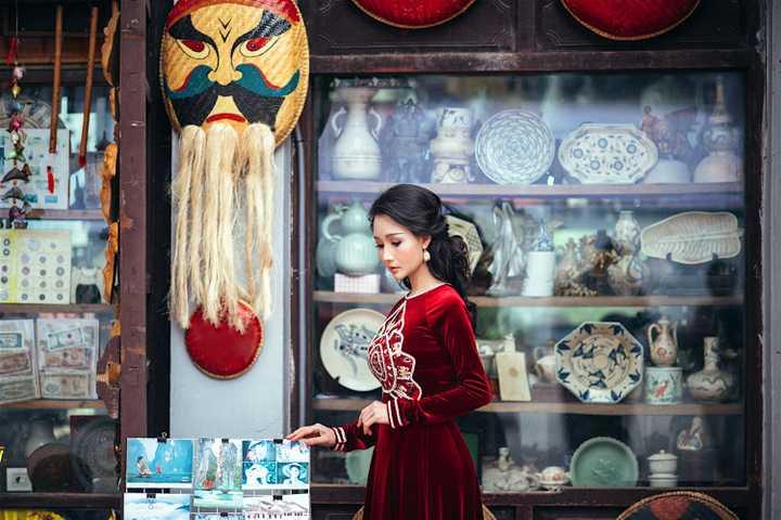 Trong các thiết kế áo dài nhung với màu đỏ đun quý phái dành cho những ngày trở lạnh, bà mẹ ba con Sương Đặng đẹp kiêu sa mà nền nã trong những khung cảnh quen thuộc của phố cổ Hà Nội