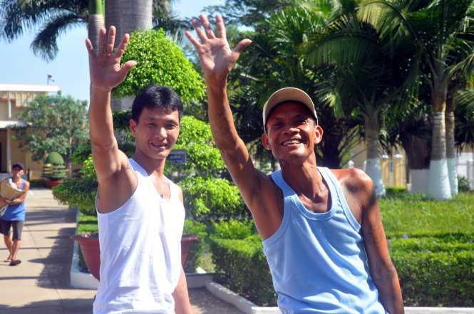 Hai người được tha tù trước thời hạn vẫy chào và động viên những người ở lại cố gắng cải tạo tốt để hưởng chính sách khoan hồng - Ảnh: Đông Hà