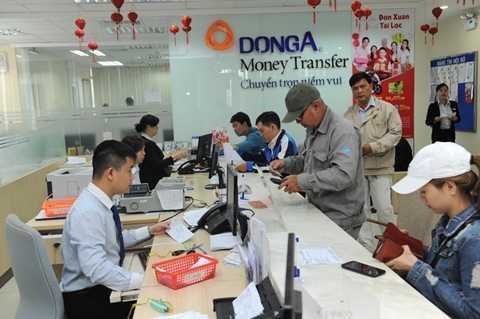 Khách hàng giao dịch kiều hối tại Ngân hàng Đông Á TP.HCM ngày 26-1 - Ảnh: Tự Trung