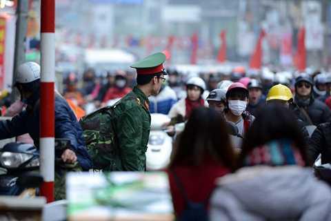 Dù đi bộ sang đường đúng quy định nhưng anh lính trẻ đành bất lực nhìn biển người tham gia giao thông