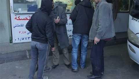 Hành khách đi Raqqa hút thuốc tại phòng vé bến xe Charles Helou ở Beirut
